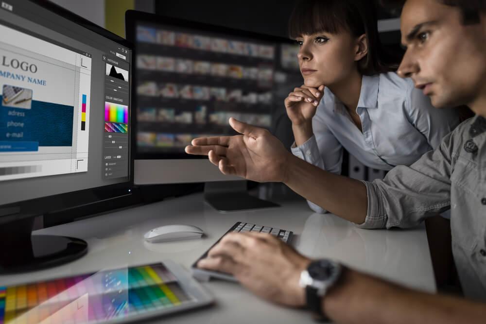dupla a frente de computadores discutindo sobre um design