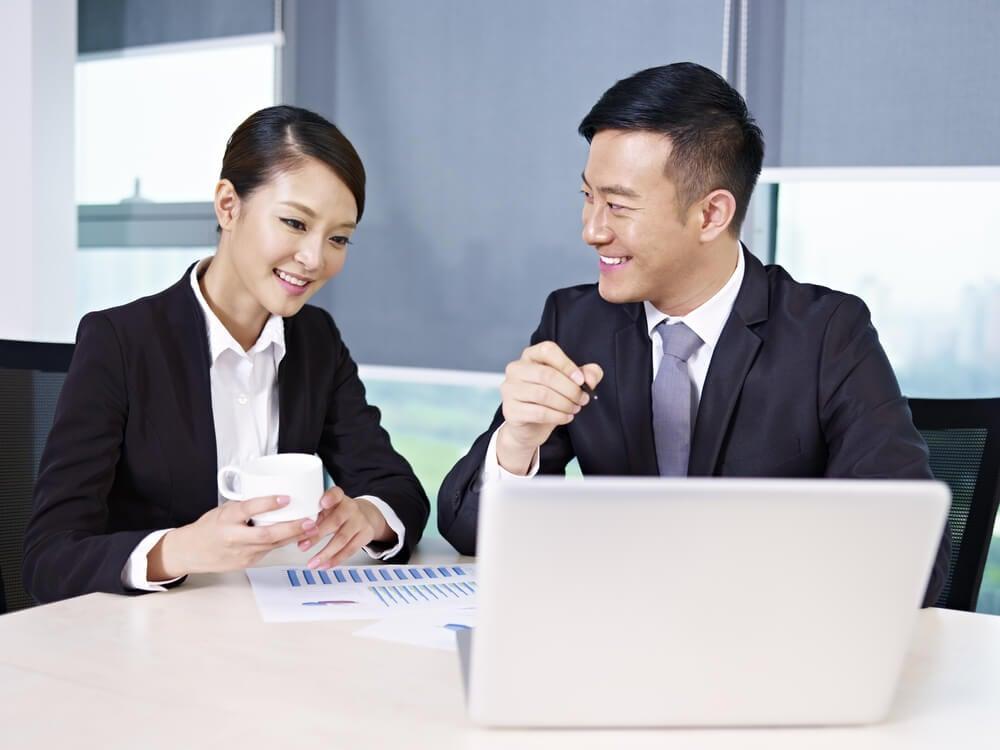dupla de colegas de trabalho sorridentes a frente de laptop