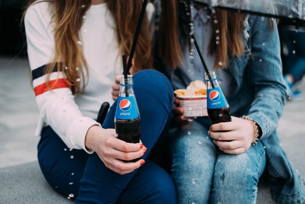 dupla de garotas com garrafas do refrigerante Pepsi
