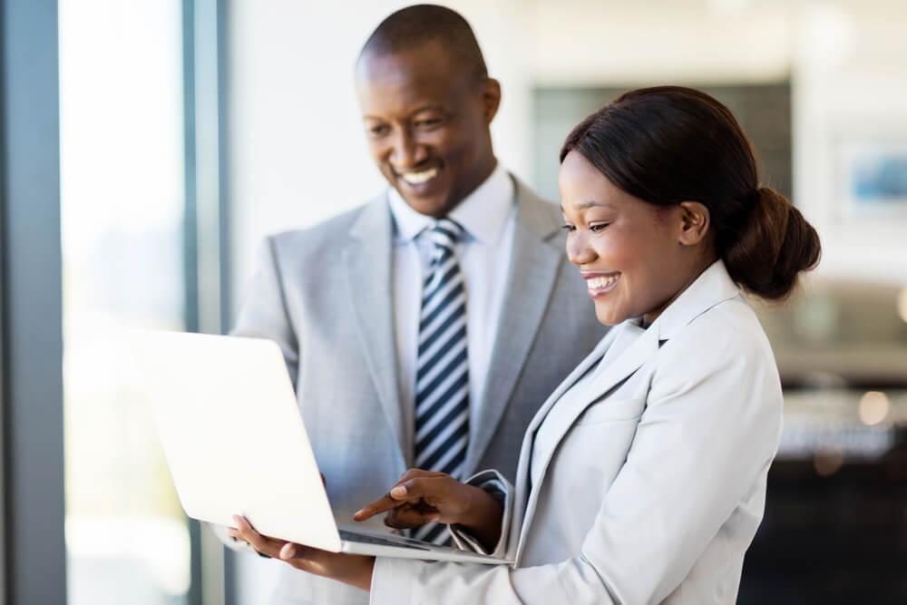 dupla de profissionais sorridentes com mulher segurando laptop