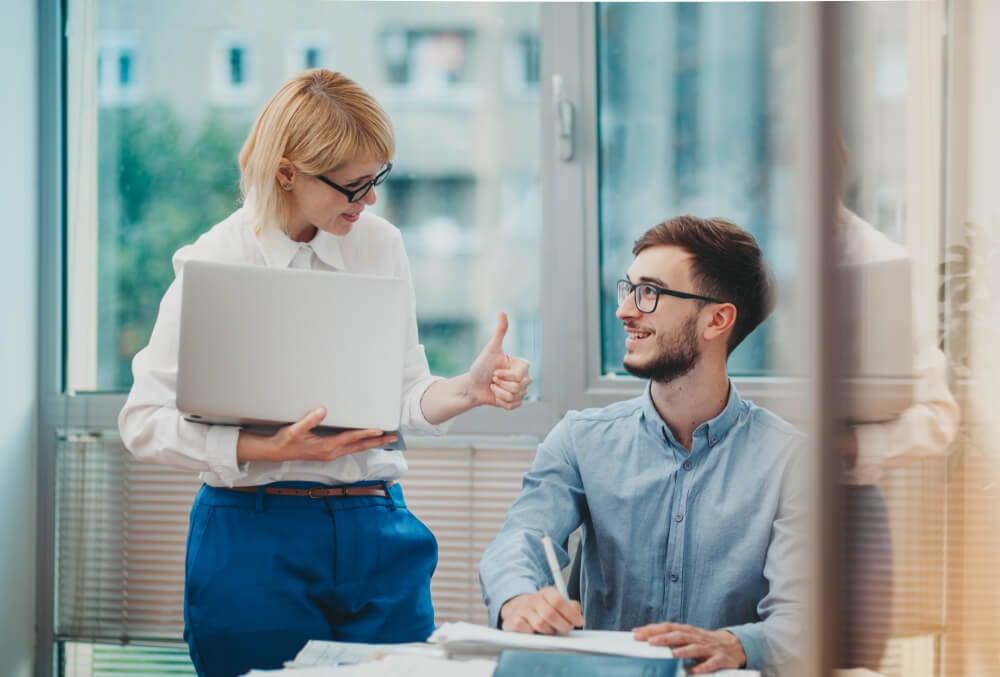 dupla em ambiente de trabalho e moça com sinal de feedback positiivo