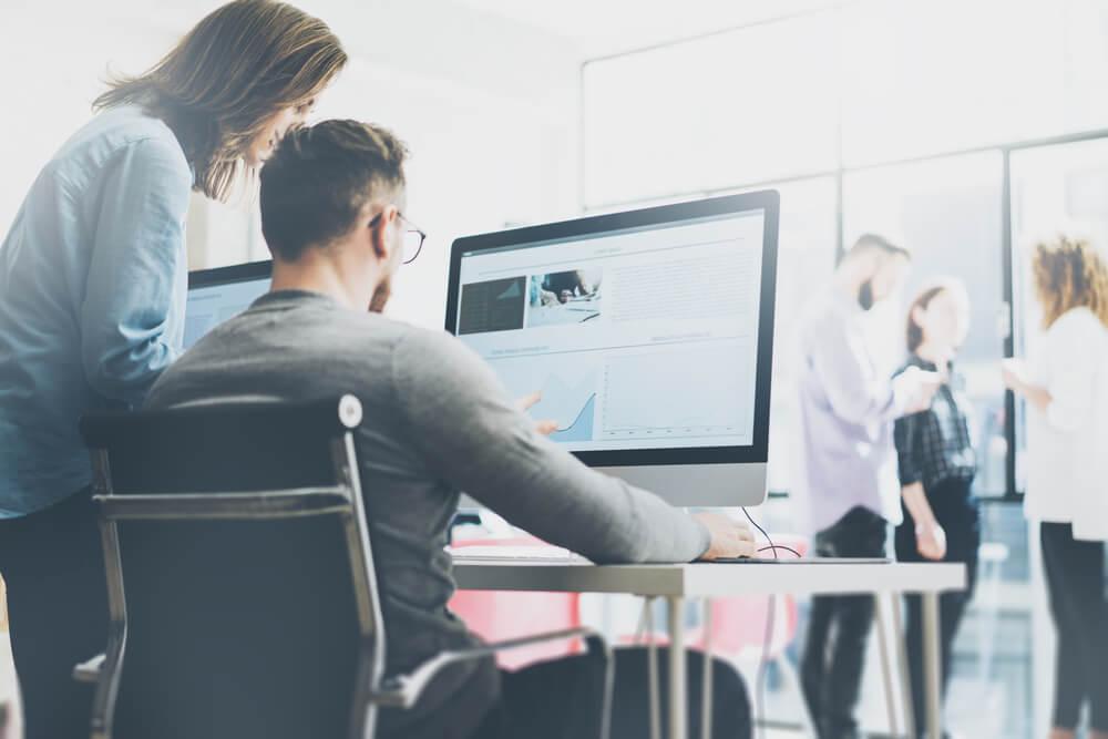 dupla trabalhando em conjunto em computador