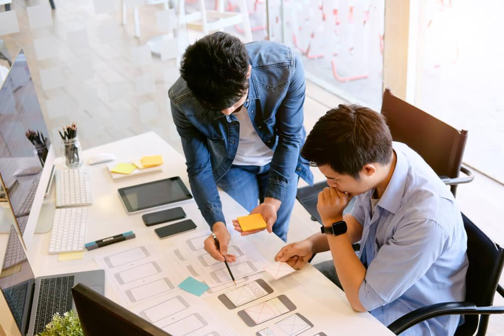dupla trabalhando em desenvolvimento de interface em escritório