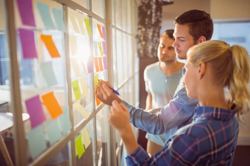 equipe criativa reunindo ideias em papeis coloridos em parede