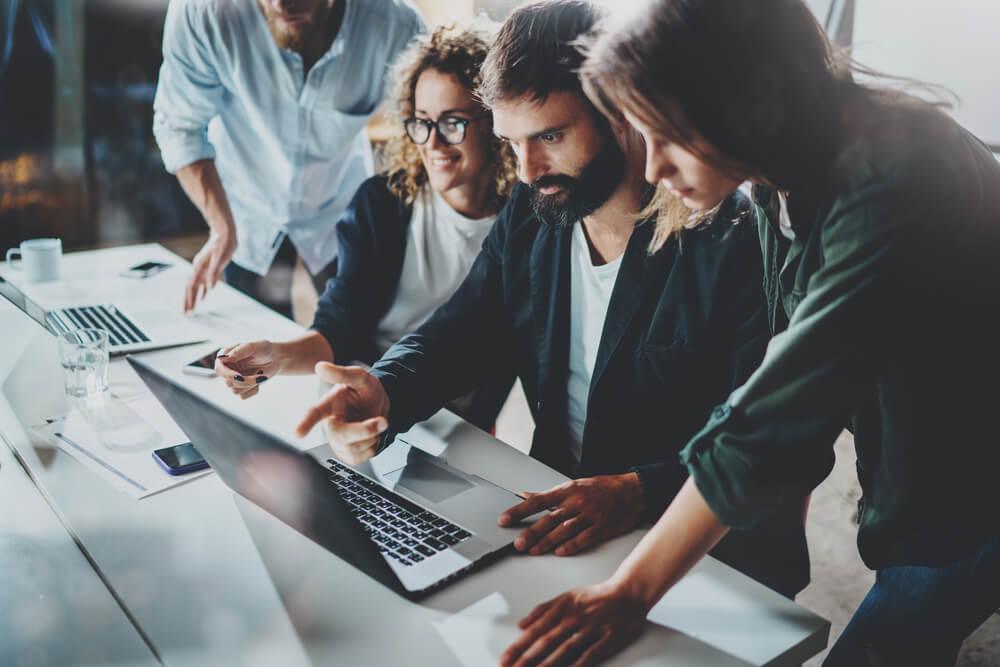 equipe de trabalho analisando dados em laptop
