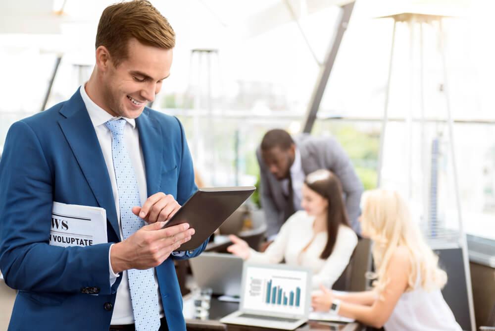 equipe de trabalho e homem em destaque sorridente com jornal e tablet