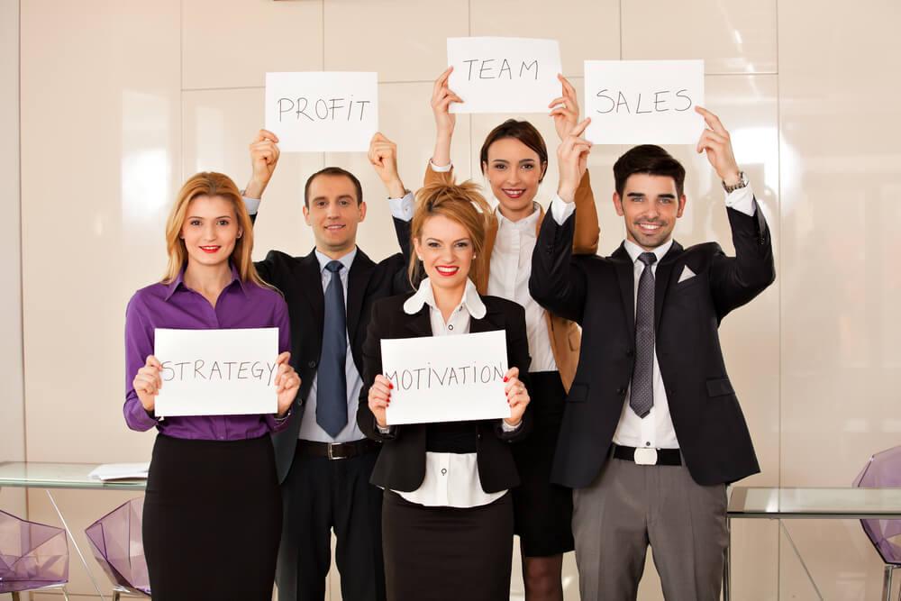 equipe de vendas com placas e palavras de motivação