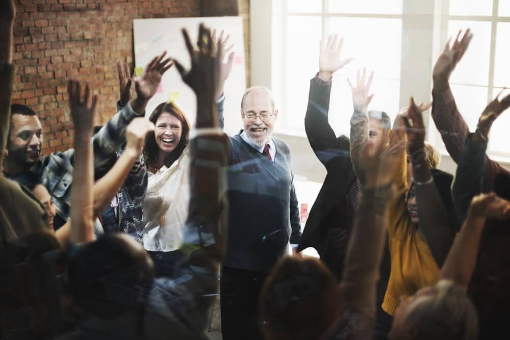 equipe em ambiente de trabalho comemorando com mãos para cima