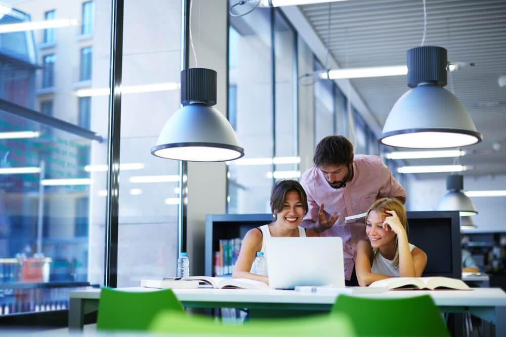 equipe sorridente acompanhando algo em laptop