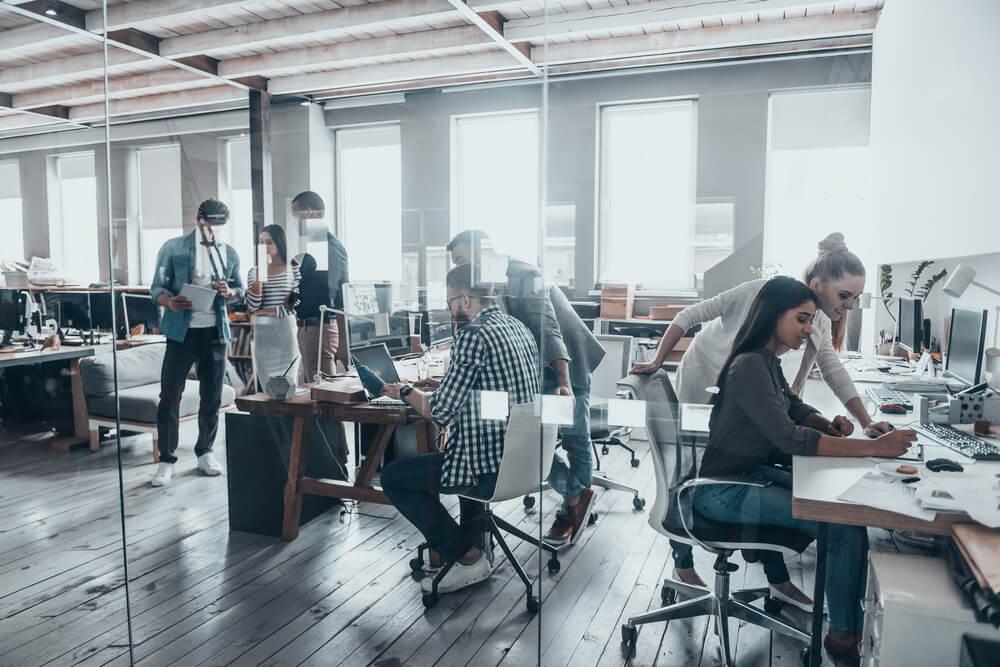 escritório com paredes de vidro e equipe trabalhando