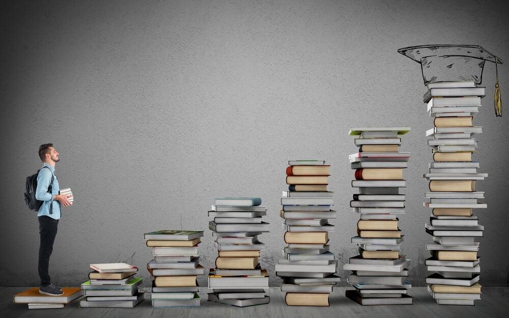 estudante a frente de escada montada de livros
