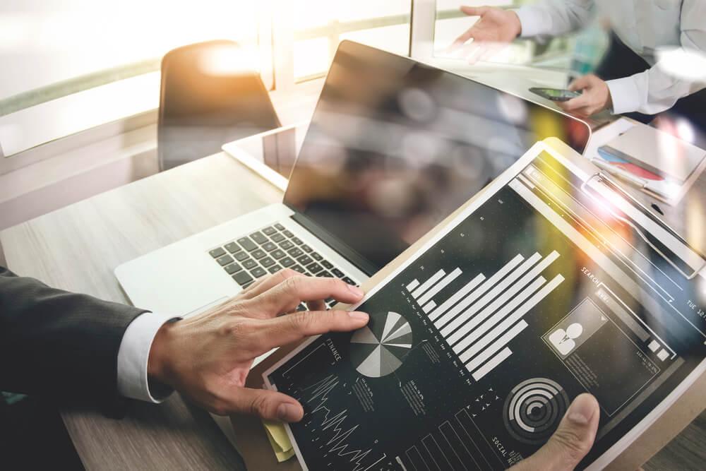 executivo segurando tablet com gráficos a frente de laptop