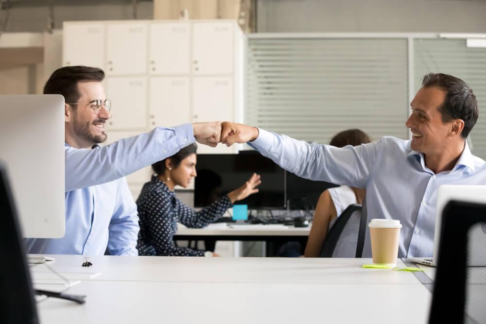 feedback positivo sendo transmitindo através de toque informal entre colegas de trabalho