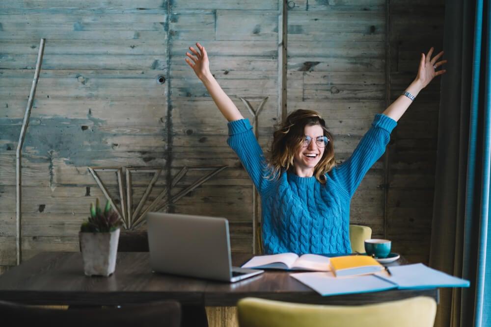 garota a frente de laptop e livros em mesa feliz e com os braços abertos e levantados