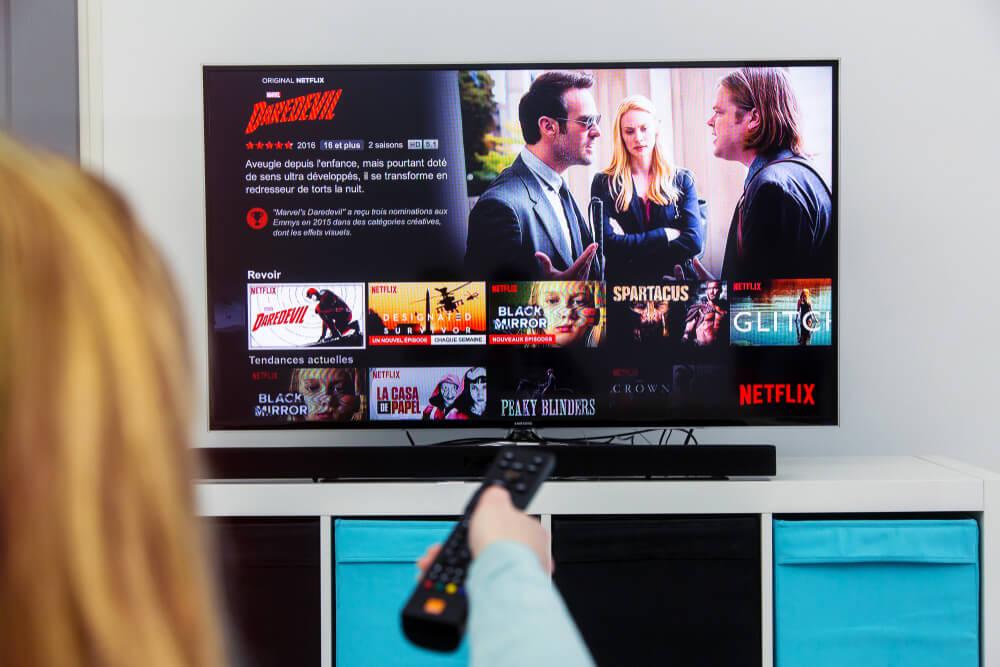 garota acessando página inicial da netflix através de TV