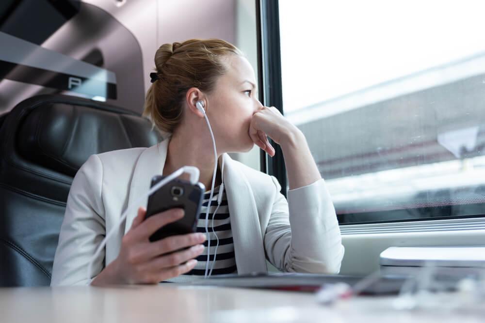 garota com fones de ouvido e smartphone distraida ao olhar pela janel