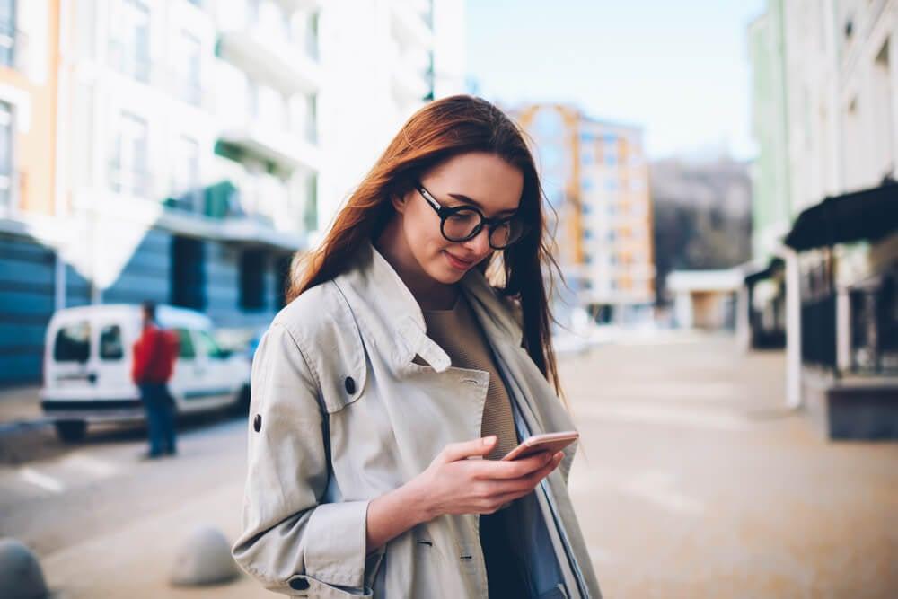 garota com sorriso tímido olhando para o smartphone enquanto caminha na rua
