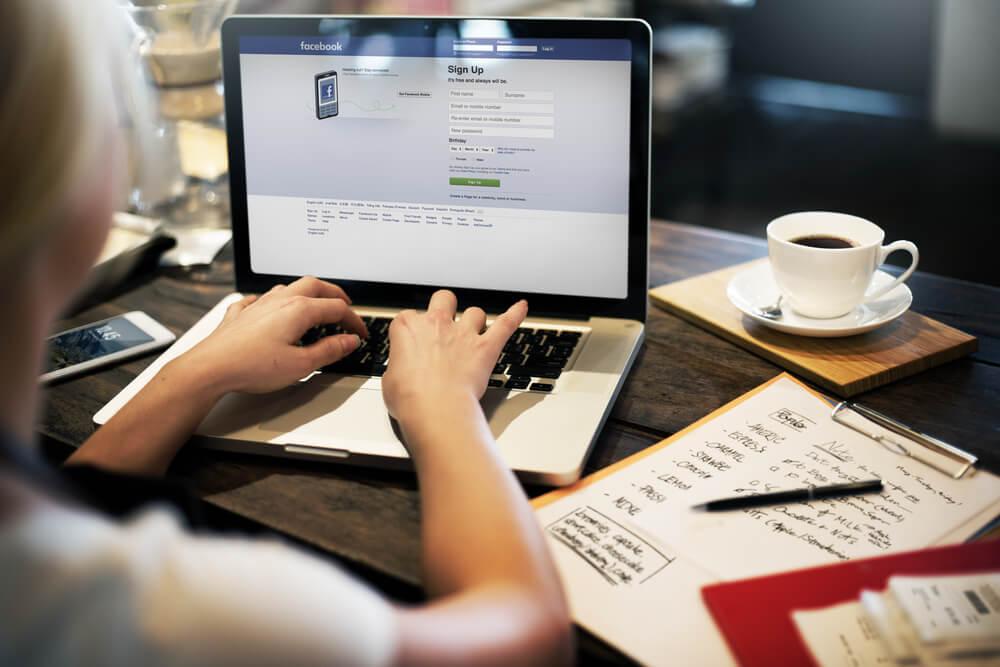 garota em café acessando facebook pelo laptop