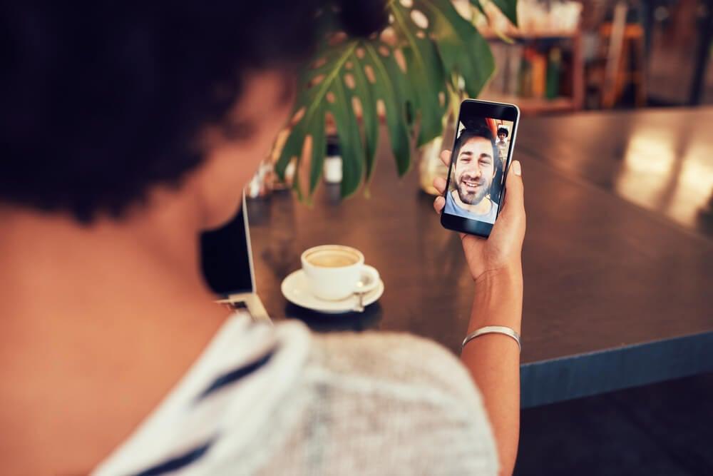 garota fazendo ligação de vídeo através do smartphone