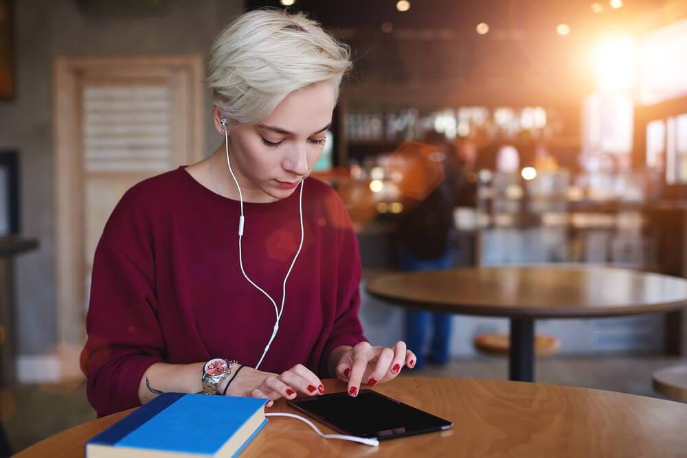 garota séria acessando smartphones e de fone de ouvidos