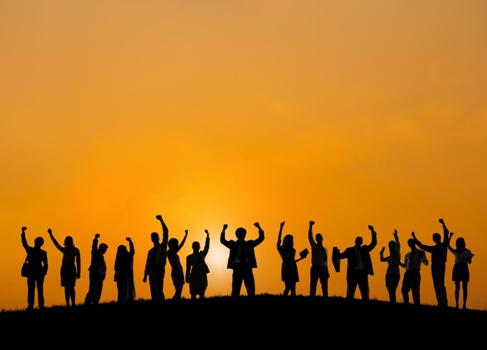 grande grupo de pessoas comemorando com braços erguidos