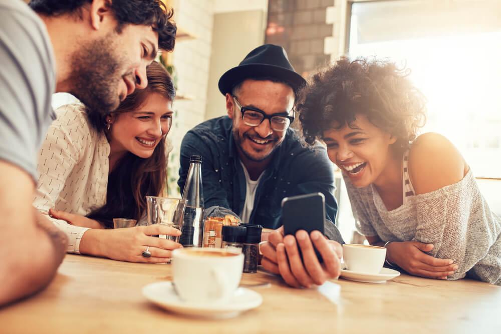 grupo de amigos sorridentes em café acompanhando algo em tela de smartphone