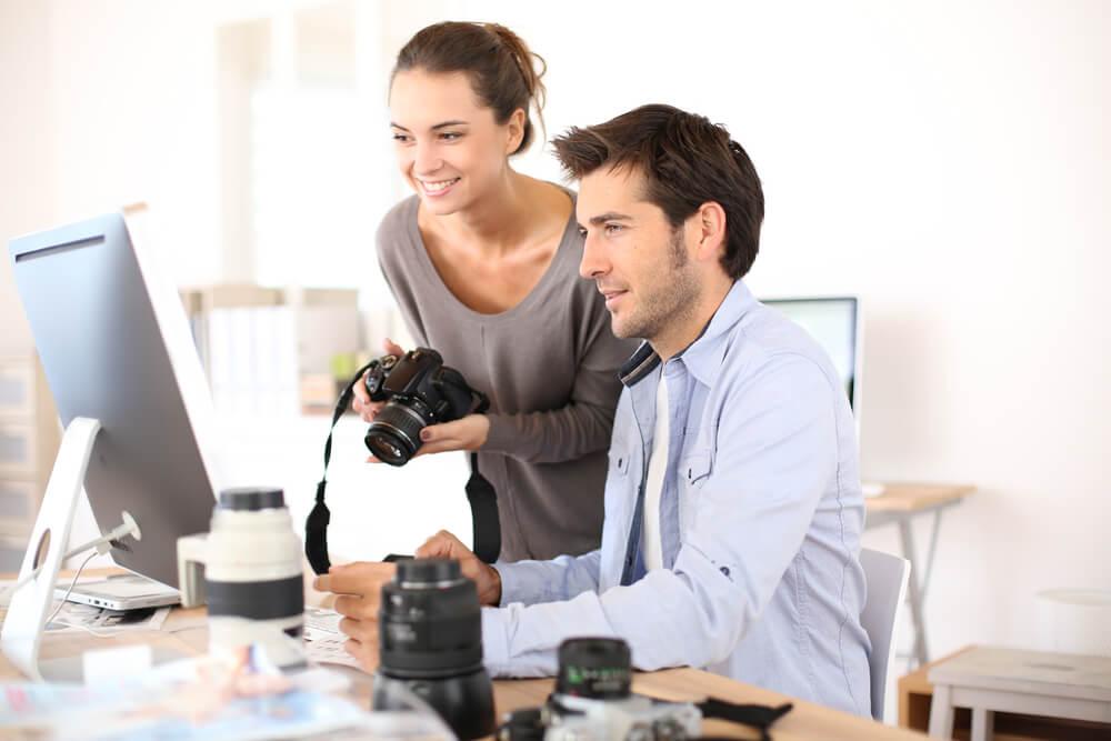 homem ao computador e mulher segurando câmera fotográfica