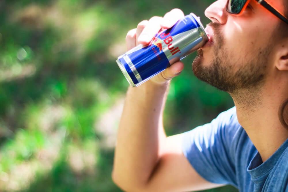 homem bebendo energético da marca RedBull