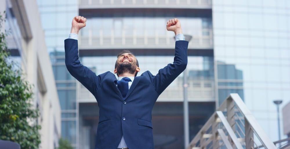 homem com vestimenta executiva comemorando com os braços para cima