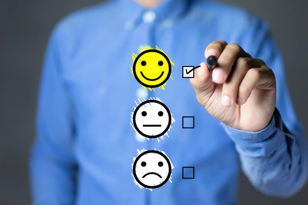 homem de camisa desfocado e mão assinalando símbolo de carinha feliz representando feedback positivo