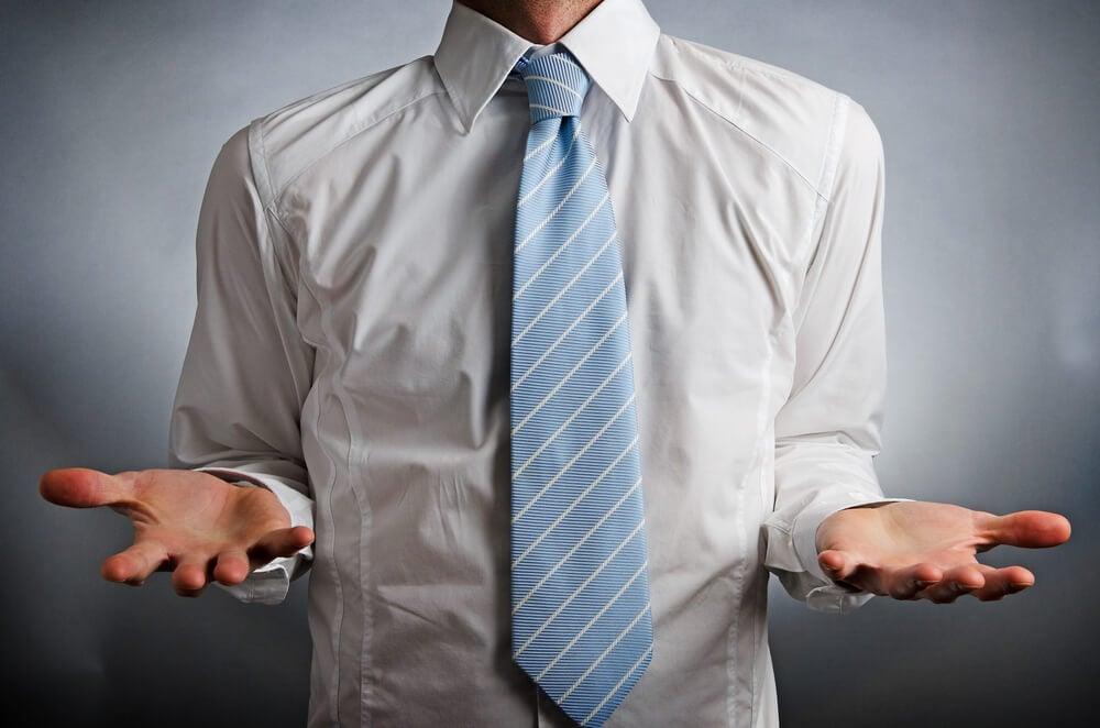 homem de camisa e gravata fazendo gesto de dúvida com as mãos