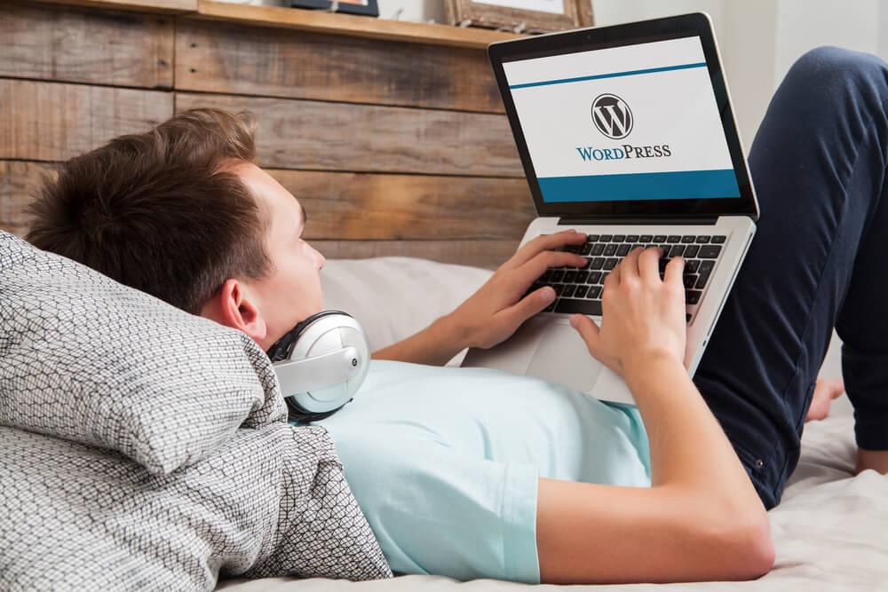 homem deitado em cama acessando no laptop site wordpress