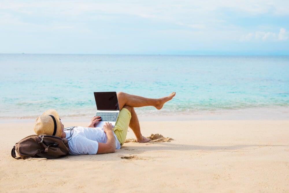 homem deitado na areia da praia com laptop no colo