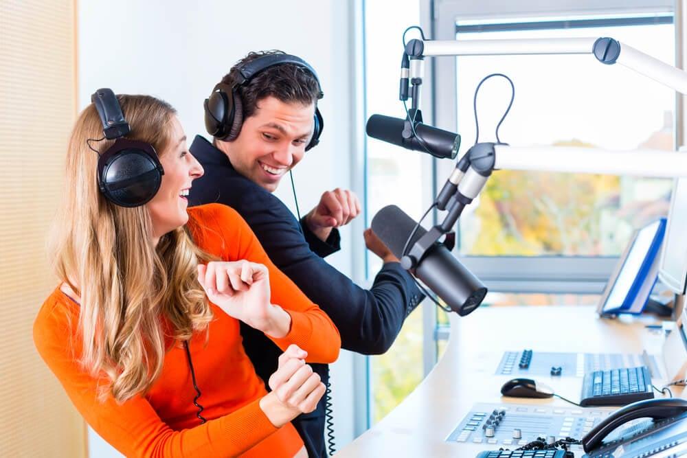 homem e mulher em gravação de programa de áudio animados e dançando