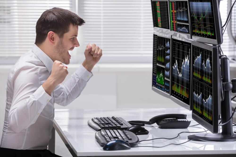 homem executivo comemorando a frente de computadores com gráficos