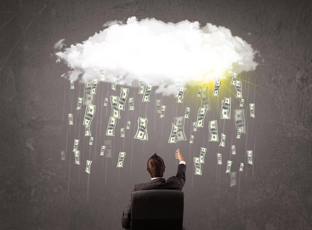 homem executivo sentado em cadeira apontando para representação de nuvem chovendo cédulas de dinheiro