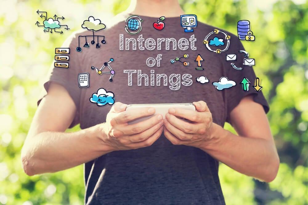 homem segurando smartphone com ilustração sobre Internet das coisas