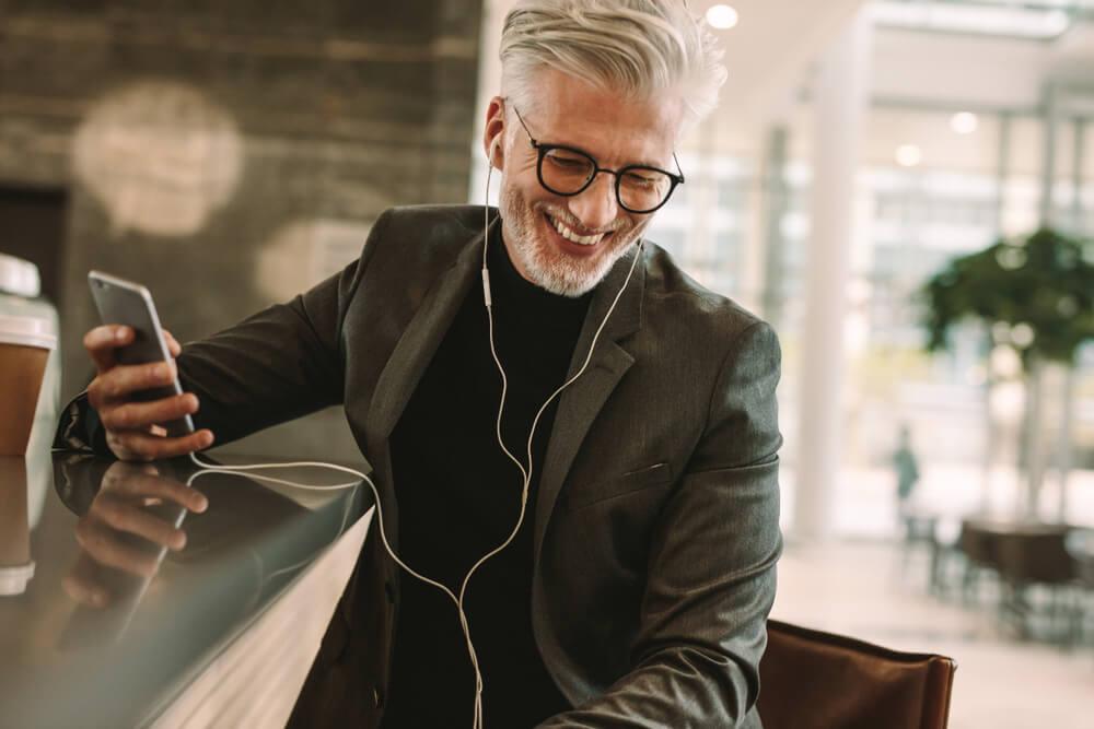 homem sorridente segurando smartphone e com fones de ouvido