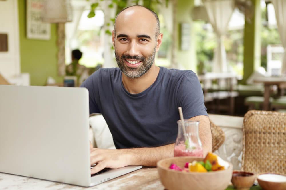 homem sorridente trabalhando em laptop em local informal