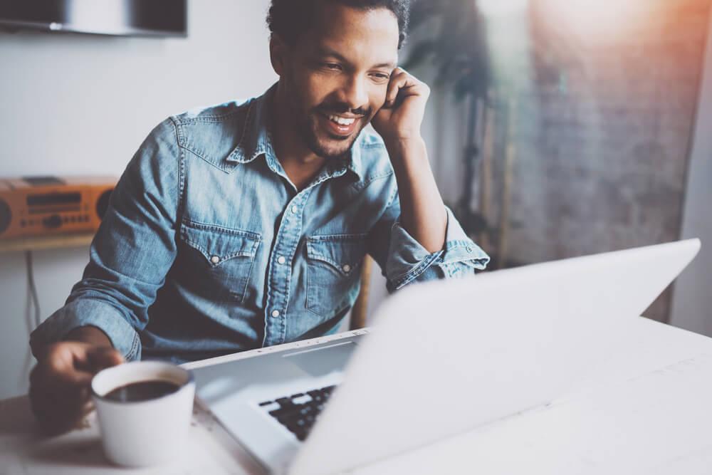 homem trabalhando em home office falando ao celular e sorridente