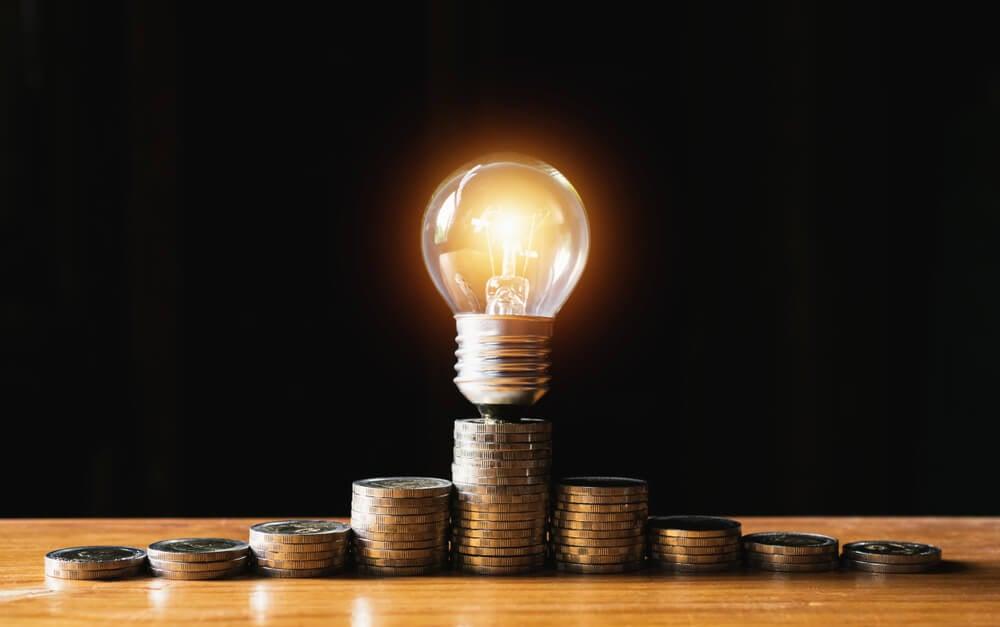 lâmpada e montes de moeda representando economia e criatividade