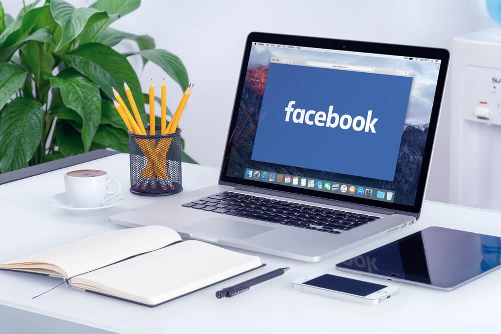 laptop acessando a rede social web Facebook com caderno de anotações ao lado