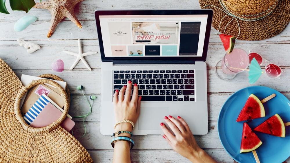 laptop acessando um site de vendas junto de acessórios de verão
