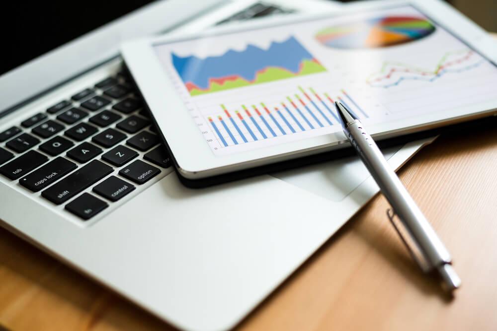laptop e papéis com gráficos