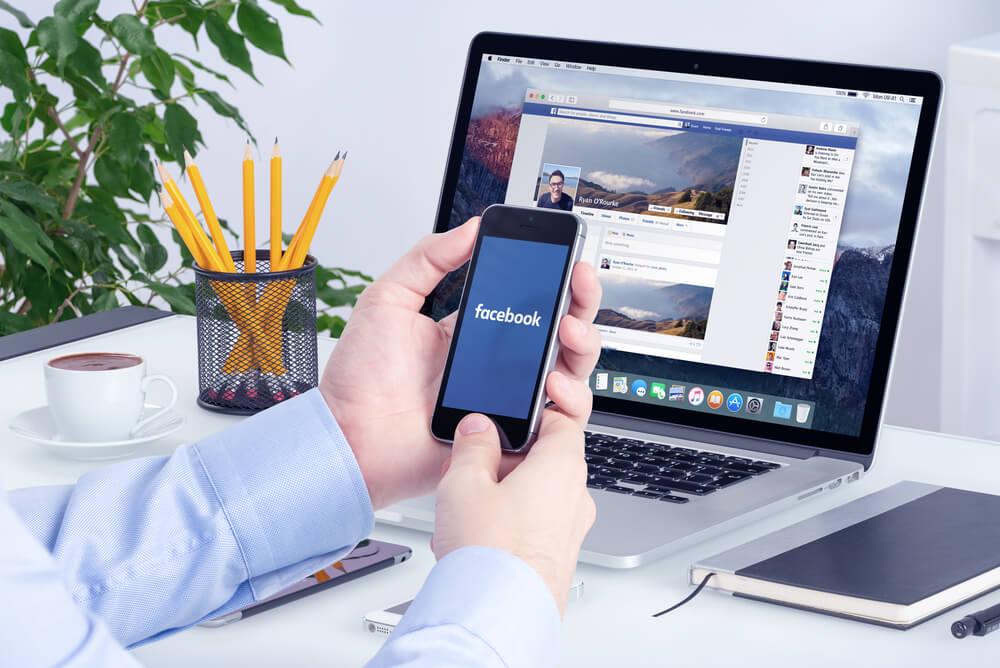 laptop em mesa de escritório com mão masculina acessando Facebook pelo smartphone