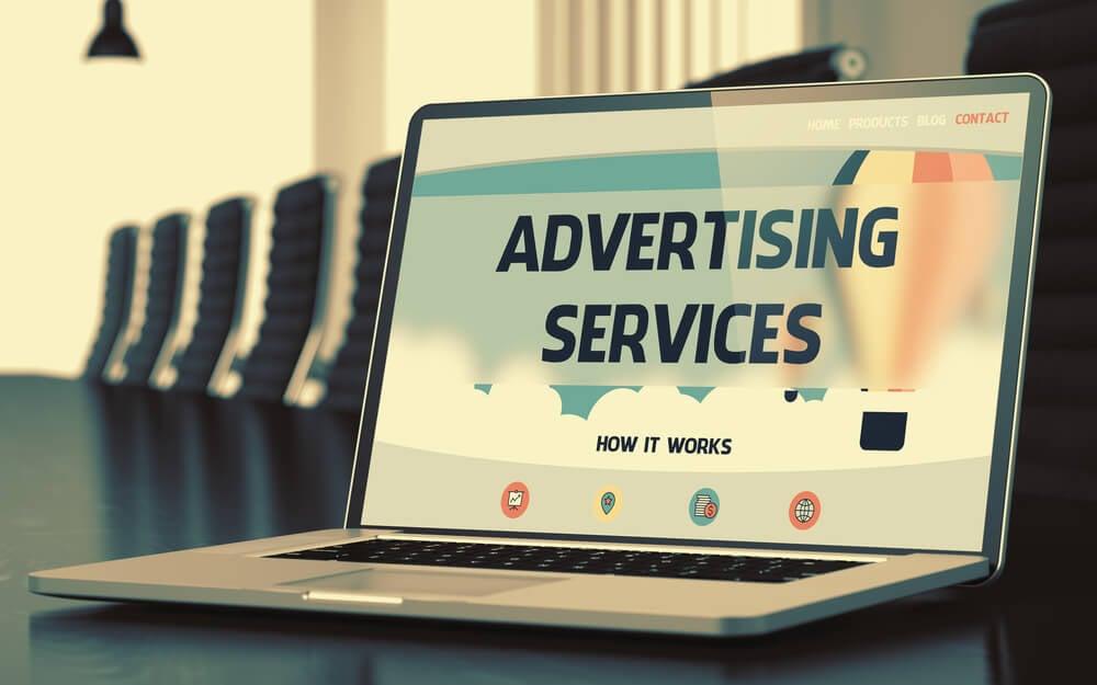 laptop em mesa de reuniões com título na tela sobre publicidade de serviços