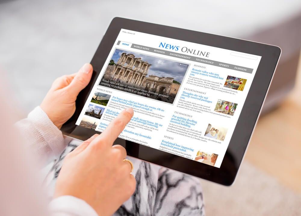 mão acessando site de notícias em tablet