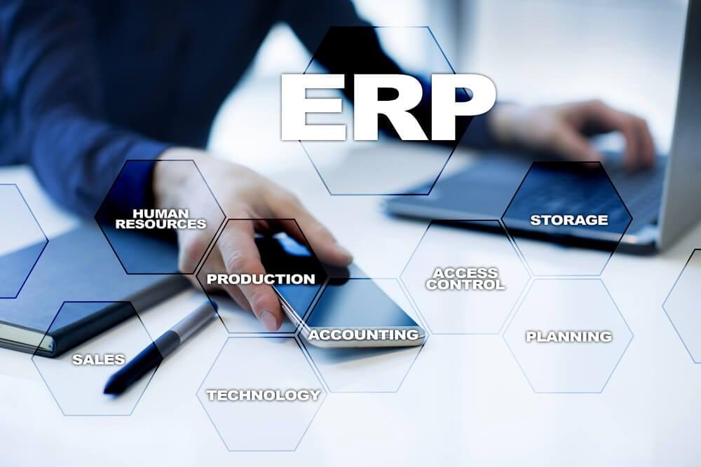 mão de executivo em mesa de escritório segurando smartphone com termos relacionados a ERP