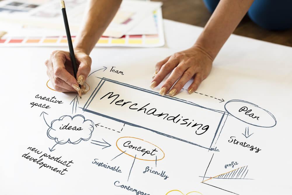 mão feminina anotando em papel sobre merchandising e termos relacionados