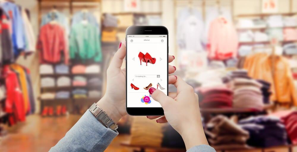 mão feminina segurando smartphone acessando item de loja virtual